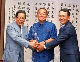 沖縄への出店計画を報告し、仲井真弘多知事(中央)と握手を交わす、エーデルワイスの比屋根毅会長(左)、比屋根祥行社長=県庁