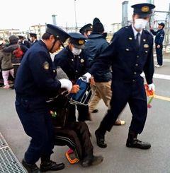 座り込みで抗議していた市民を、強制排除する警察官=31日午前7時30分ごろ、名護市辺野古のキャンプ・シュワブゲート前(下地由実子撮影)
