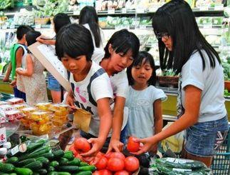 買い物学習のミッション「実を食べる野菜」で、トマトを選ぶ子どもたち=23日午前、那覇市・コープあっぷるタウン