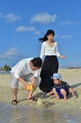 ぽかぽか陽気の青空の下、波打ち際で遊ぶ親子連れ=21日午後4時すぎ、豊見城市・豊崎美らSUNビーチ(金城健太撮影)