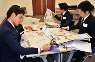 新聞を読んで気になる記事を探すコザ信金の新入社員=13日、沖縄市・コザ信金本店