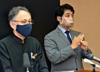 口元が見えるよう透明のマスクを着け、玉城デニー知事の会見内容を手話通訳する男性(右)=19日、県庁