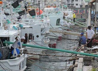 台風12号の接近に備えて、係留の準備をする漁師ら=31日午前11時ごろ、那覇市・泊漁港