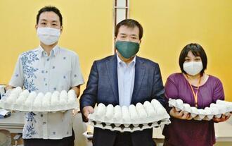 「こんな時だからこそ、おいしいゆで卵を食べて元気になってほしい」と話す前田睦己社長(中央)ら=23日、那覇市港町