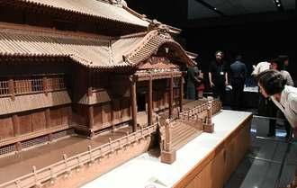 県立博物館・美術館で初めて展示される「首里城正殿模型」に見入る来場者=23日、那覇市おもろまち