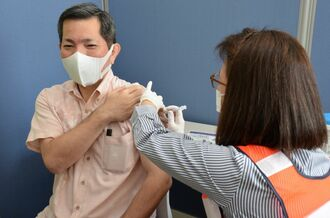 新型コロナウイルスワクチンの接種シミュレーションに参加する山川仁豊見城市長(左)=11日、沖縄県豊見城市