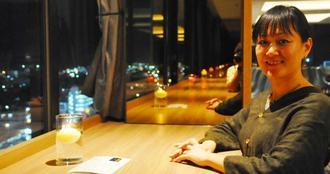 """香り""""X""""を分解したキャンドルを前に笑顔を見せるMAKI UEDAさん=石垣市大川・アートホテル石垣島のスカイバンケット&バー「カプリコン」"""
