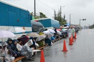 雨の中、座り込んで新基地建設に抗議する市民ら=22日、名護市辺野古、米軍キャンプ・シュワブゲート前
