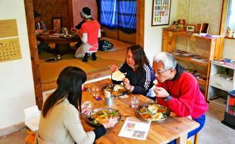 古い民家を改装した店内で食事を楽しむ客=本部町伊豆味・スーリヤ食堂