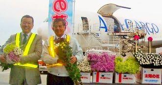 キクの花をPRする宮城重志組合長(右)とANACargoの谷村昌樹沖縄統括室長=8日、那覇市・那覇空港貨物ターミナル