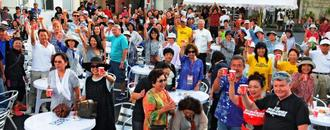 初の「世界の久米島ンチュ大会」の前夜祭で、乾杯する海外移住者や住民たち=24日夕、久米島町仲泊の新興通り駐車場