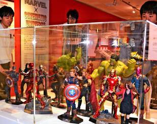 マーベルのヒーローのフィギュアを見る入場者=11日、那覇市・デパートリウボウ(©2017MARVEL)