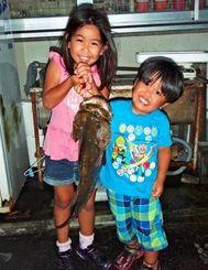 三重城海岸で2.79キロのミーバイを釣った新田かなさんとなお君(左から)=1日