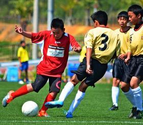 県内のサッカーチームと試合をした熊本市の子どもたち(左)=3日、金武町(伊藤和行撮影)