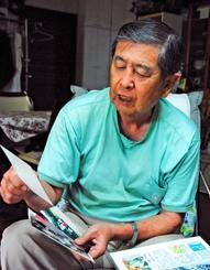 山本朝保さんの写真を見て、特徴をなつかしそうに話す長男の勇さん=27日午前、宜野湾市我如古の山本さん宅