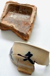 久茂地尋常小学校跡地から発掘された茶碗と硯。茶碗には久茂地の「久」が記されている=13日、、那覇市・久茂地小学校跡地