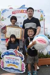 入園者1億人目となった佐野拓磨ちゃん(前列右)と妹の志織ちゃん(同左)、父親の直樹さん(後列右)と母親の美幸さん(同左)=3日、本部町・海洋博公園
