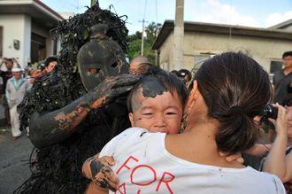 島尻のパーントゥで、泥を塗られる子ども。1年間の無病息災が約束されるとされ、保護者が我が子を連れて泥塗りをお願いする=2014年10月3日、宮古島市平良島尻