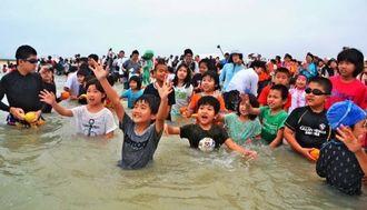海に投げ入れられる果物を取ろうと手を伸ばす子どもたち=石垣市南ぬ浜町