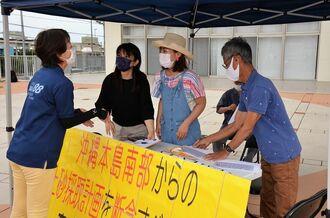沖縄戦の戦没者の遺骨を含んだ土砂の使用に反対し、署名する市民ら=3日、豊見城市役所前