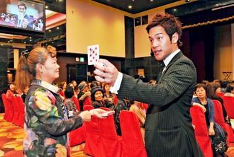 会員に参加してもらいマジックを披露するマサ・マジックさん=8日、那覇市の沖縄かりゆしアーバンリゾート・ナハ