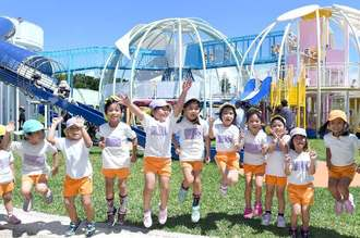 県平和祈念公園・子供の広場に設置された新大型遊具「命の卵」の前で遊ぶ園児=28日、糸満市摩文仁(下地広也撮影)