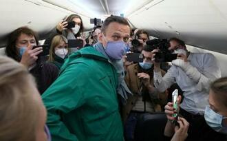 モスクワに飛び立つ前の機内で記者団に囲まれるナワリヌイ氏=17日、ドイツ・ベルリン近郊の空港(AP=共同)