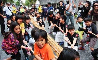 懸命に綱を引く子どもたち=6日、那覇市東町サンシャイン通り付近(実行委員会提供)