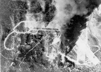 10・10空襲で米艦載機の爆撃を受けて炎上する旧日本海軍小禄飛行場=1944年10月10日(県公文書館所蔵)