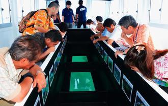 海底遊覧船「アークレックス ワン」から海底をのぞく乗客ら=31日、那覇市