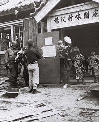 米第10軍歩兵部隊に占領された座間味村役場で、米軍政府布告を見入る住民=1945年
