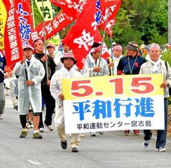 「宮古に自衛隊はいらない」などと書かれたのぼりを掲げ歩く参加者=10日、宮古島市内