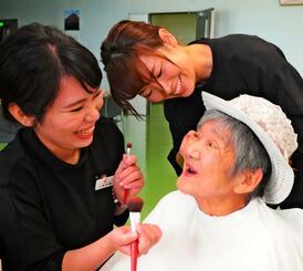 「真徳苑」に入所するトミさん(右)に化粧を施す沖縄ワタベウェディングのスタッフたち