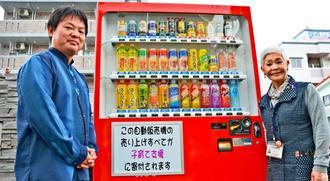 子ども支援のための販売機を設置した喜友名曜一さん(左)と、寄付に感謝する市社会福祉協議会の積靜江会長=2月20日、沖縄市海邦