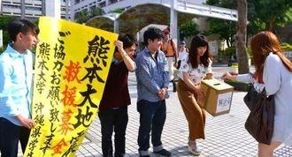 道行く人から募金を受け取る熊本大の学生ら=19日、那覇市・県民広場前