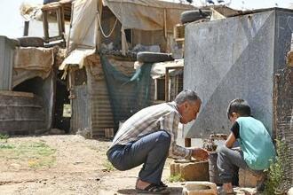 難民キャンプで手を洗うシリア人の男性と子ども=4月20日、レバノン・バールベック・ヘルメル県(共同)