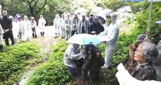広島経済大の学生らを前に沖縄戦の体験を話す上原米子さん(右)=3日、本部町・八重岳野戦病院跡