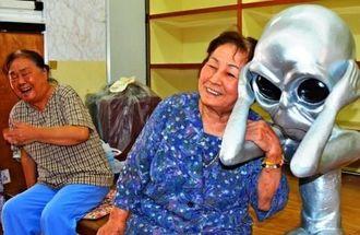 宇宙人に寄り添う(右から)具志美津子さんと小嶺静子さん=18日、牧志公設市場衣料部