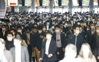 マスクを着けて通勤する人たち=23日朝、東京・品川駅