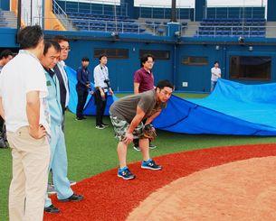 関係者とともに新球場を視察する阿部慎之助さん(中央)=6日、伊江村(村役場提供)