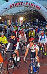 一斉にスタートする本島一周サイクリングなどの参加者=8日午前7時すぎ、名護市・21世紀の森体育館前(国吉聡志撮影)