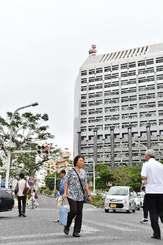 梅雨入りした沖縄地方。雨雲の下、足早に歩く人たち=8日午前、那覇市久茂地