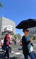 晴天の下、日傘を差して交差点を渡る歩行者=14日午後3時すぎ、那覇市久茂地(田嶋正雄撮影)