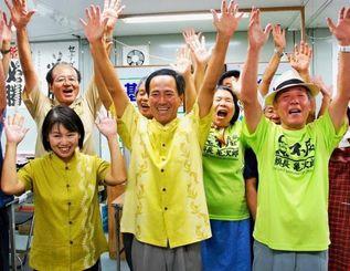 初当選を喜び万歳する瀬長美佐雄さん(中央)=5日午後10時すぎ、豊見城市根差部の選対事務所