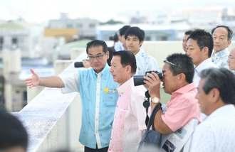 佐喜眞宜野湾市長(左)に案内され普天間飛行場を視察する江崎沖縄担当相(前列左から2人目)=9日午前10時52分、宜野湾市役所