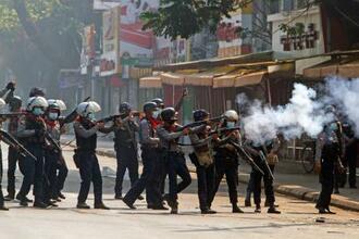最大都市ヤンゴンで催涙ガスを発射する治安部隊=28日(ロイター=共同)