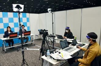 オンラインによる合同説明会で学生に自社の魅力をPRする採用担当者(左側の2人)=1日午前、東京都内