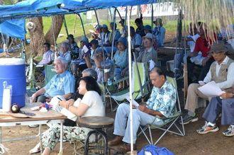 集会で辺野古総合大学の説明を聞く市民ら=26日、名護市辺野古キャンプ・シュワブゲート前
