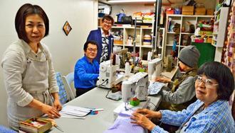 バックの縫製を手掛ける「アジュテ」の利用者と職員ら=うるま市石川赤崎「アジュテ」