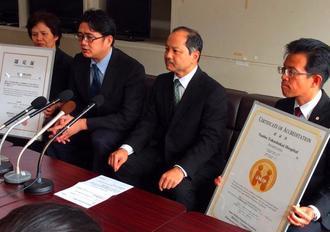 認証取得を発表する南部徳洲会病院の赤崎満院長(右から2人目)と大城安之・国際医療支援室長(同3人目)ら=21日、県庁